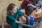 Claire Cowden, an MD/MBA student, performs an exam on a child at Bawaleshie School. Photo: Jordi Owusu