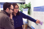 Xinghui Chen, a doctoral student in marketing, discusses her research on charitable giving with Joshua Khavis, assistant professor of accounting and law.