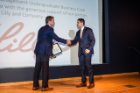 Noah Nardozza, a business administration student in the UB School of Management, accepts his award for Best Presenter among all undergraduates in the competition.