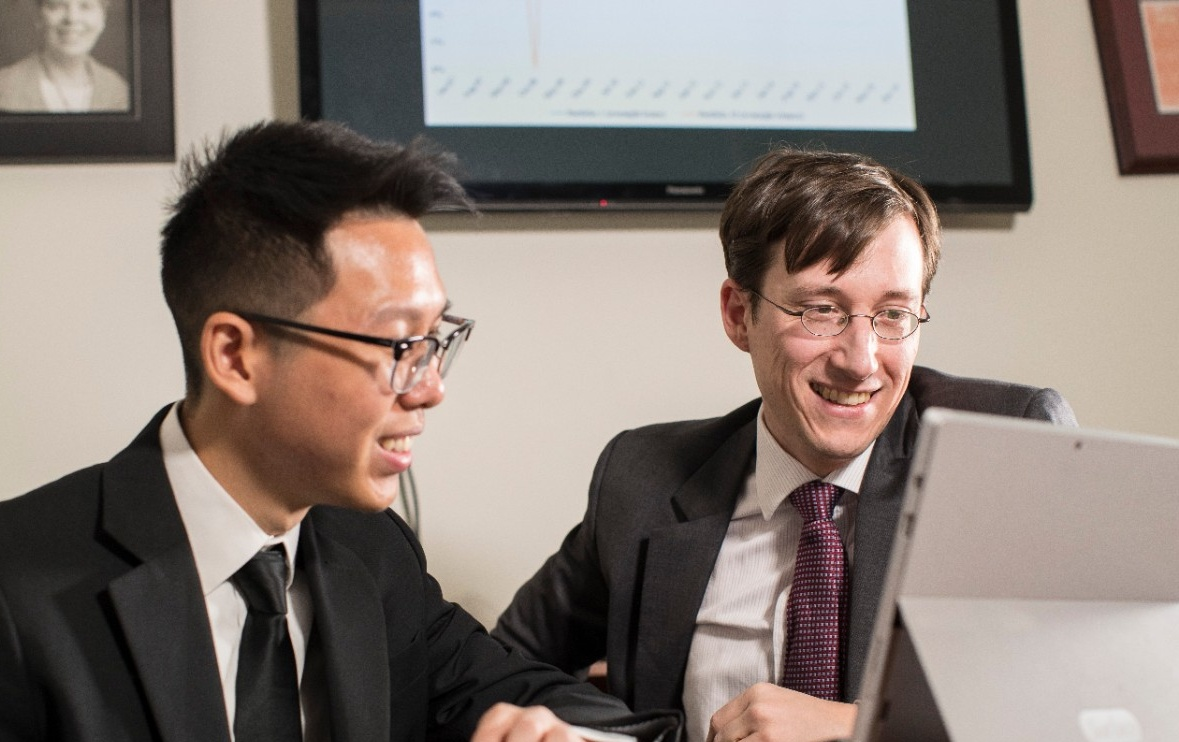 Michael Leung and Professor Dominik Roesch look over the undergrad's stock trading strategy research.