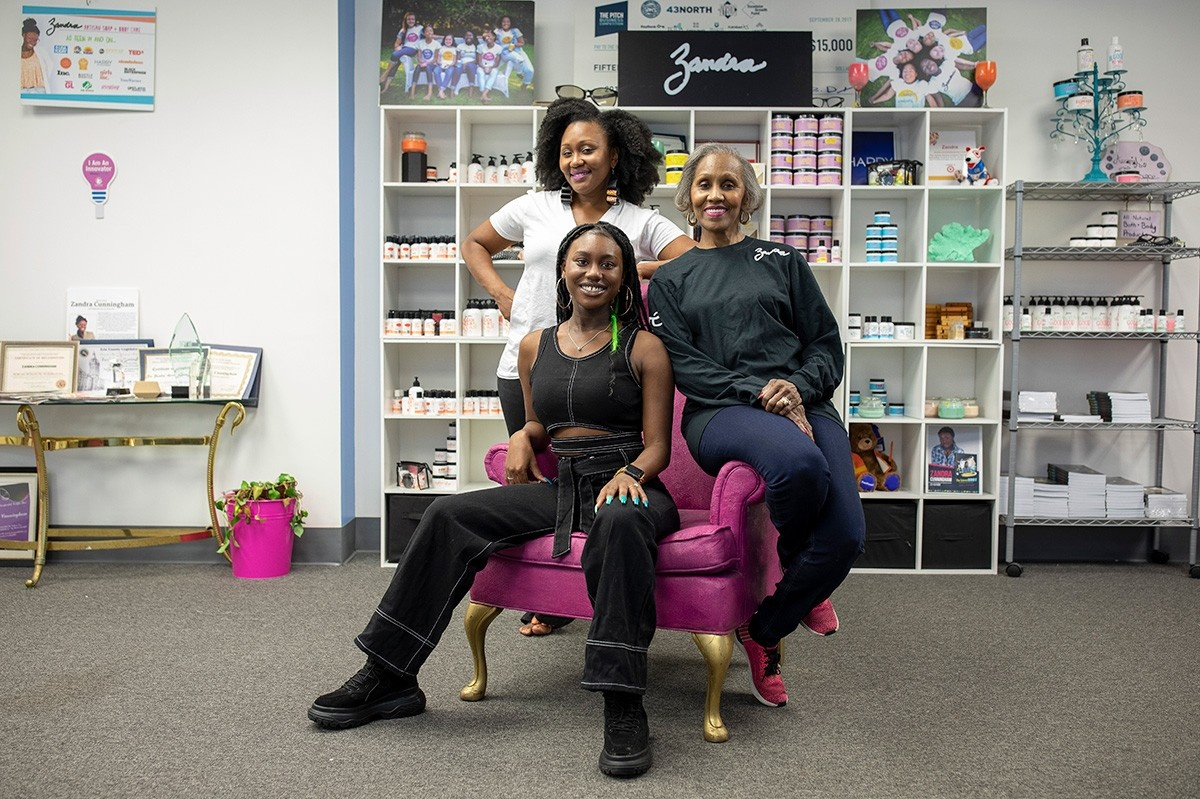 Tamara Lewis-Cunningham, MWEE '07, Zandra Cunningham, MWEE '14 and Zandra Lewis, MWEE '07, pose in the showroom of their Pierce Arrow Commerce Park production facility.