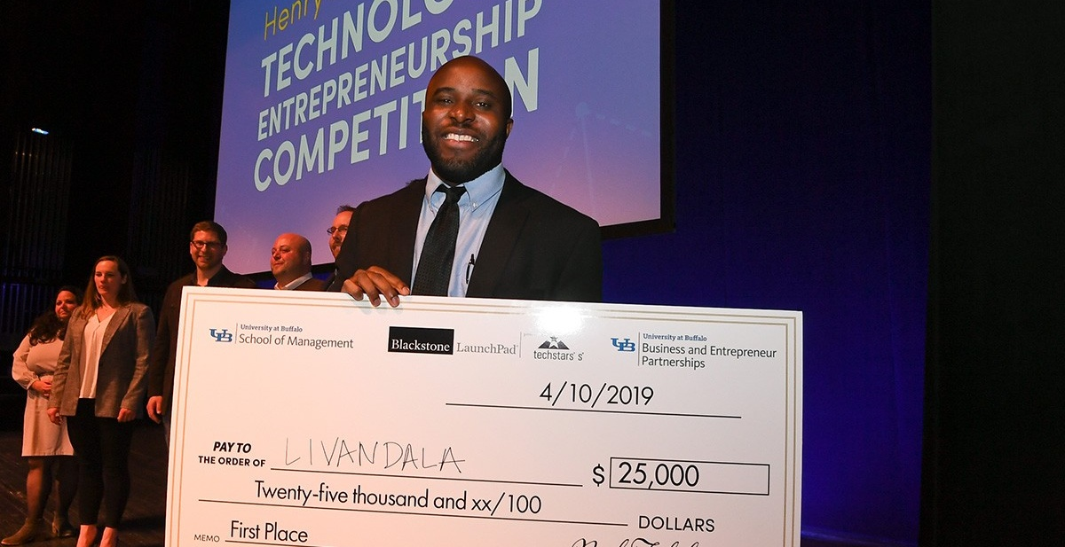 Ogechi Ogoke with a big check for $25,000 after winning first place in the 2019 Panasci Technology Entrepreneurship Competition.