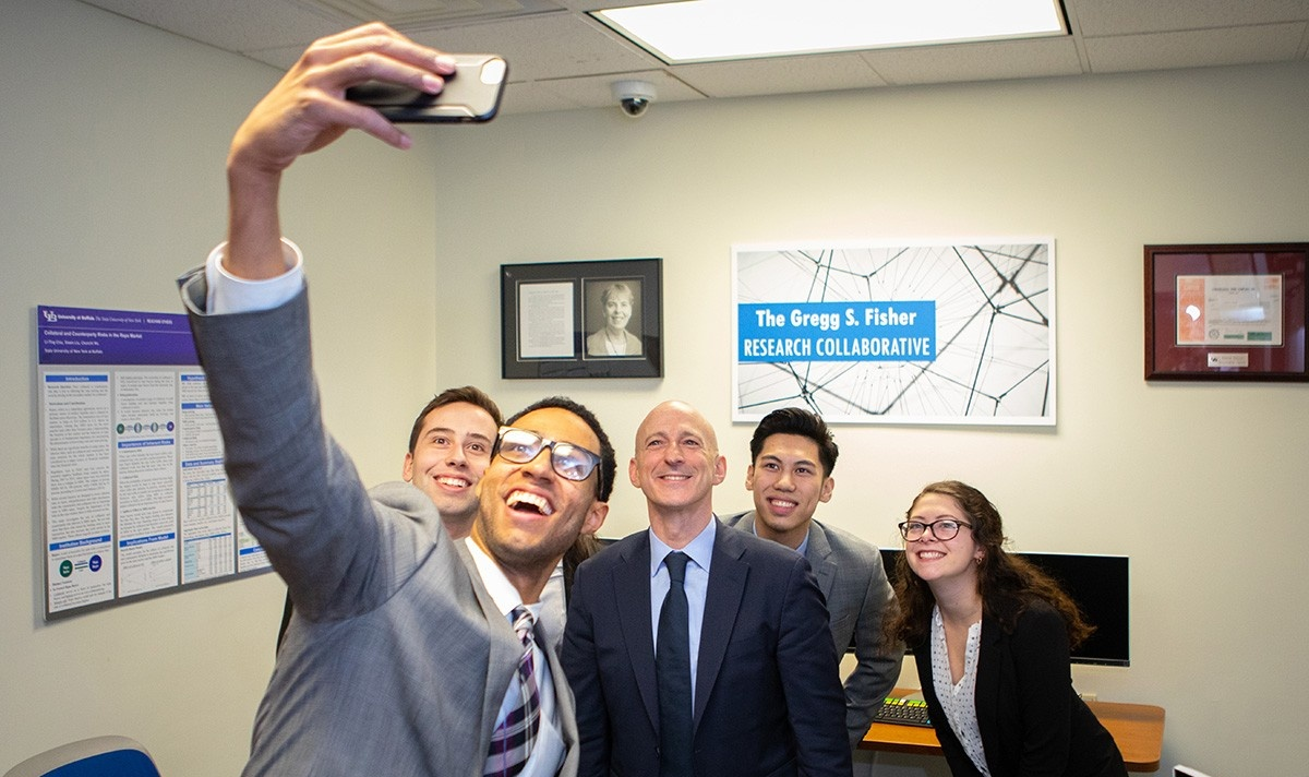 Fisher takes a selfie with students in the Fisher Research Collaborative at the UB School of Management.