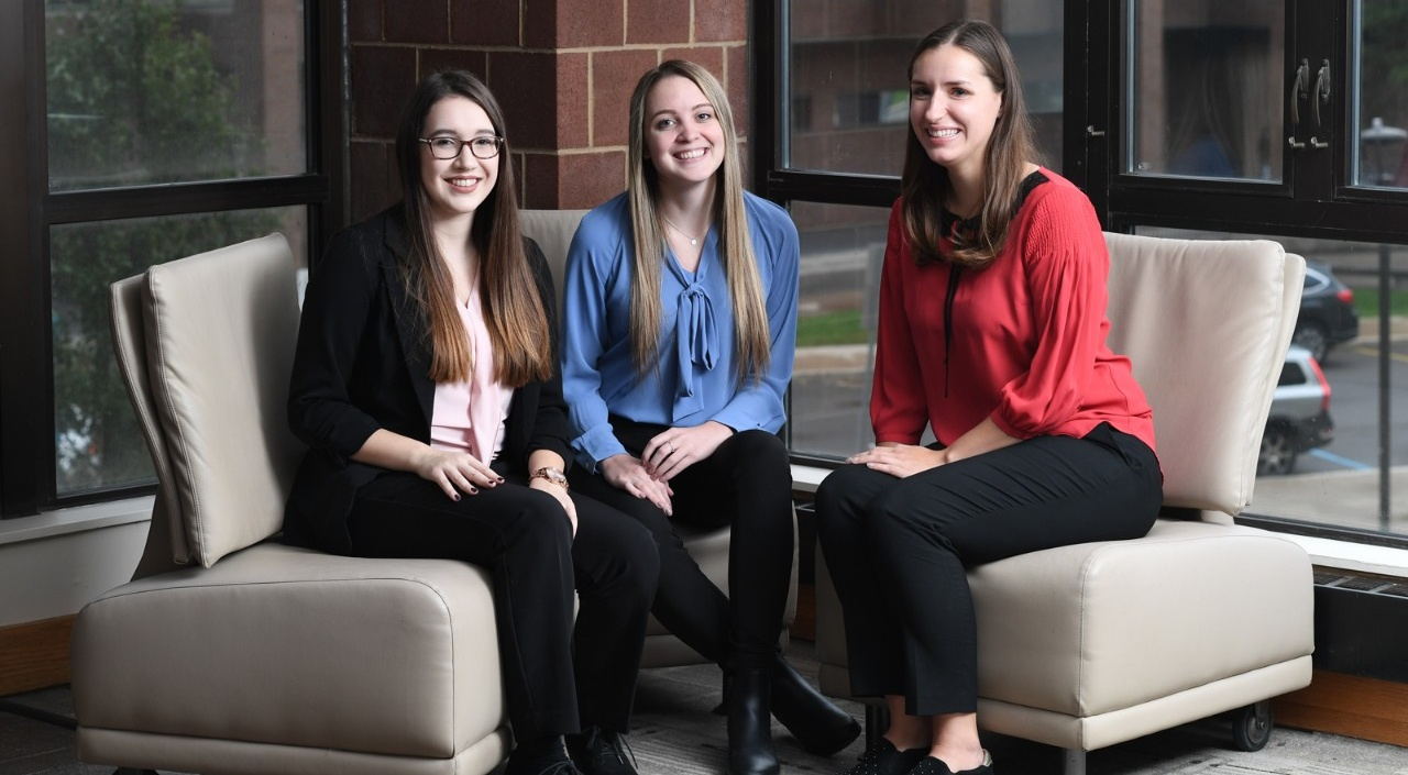 From left, Women in Management e-board members Jenna Behm, Samantha Frank and Gabrielle Lindauer sit on chairs in Jacobs Management Center.