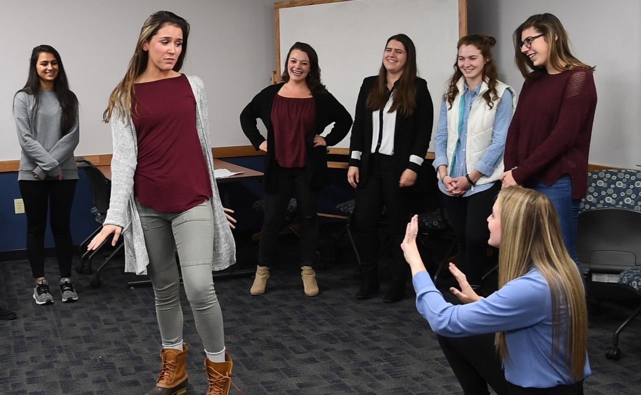 During an improv workshop, one young woman plays a photographer and another plays a model, while several other students look on.