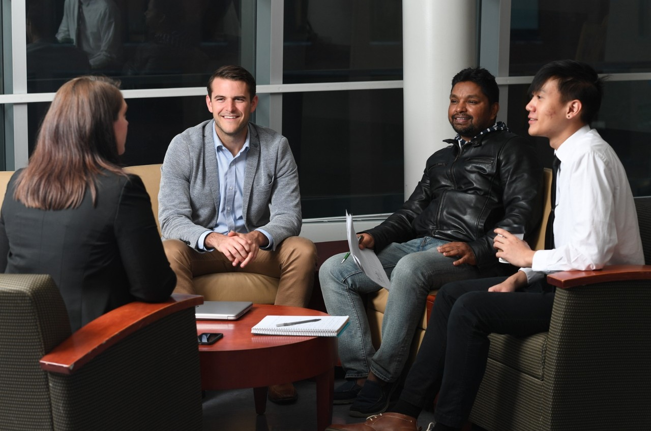 Katie Andrews, assistant director for recruitment and marketing in the school's Center for Executive Development, talks with students Harrison Steinwald, Chinmay Das and Chetinai Kalamaphichit in the Alfiero Center atrium.