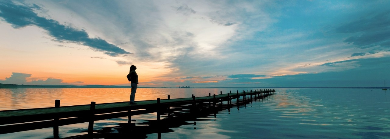 Woman standing on a pier, hopeful for the future.