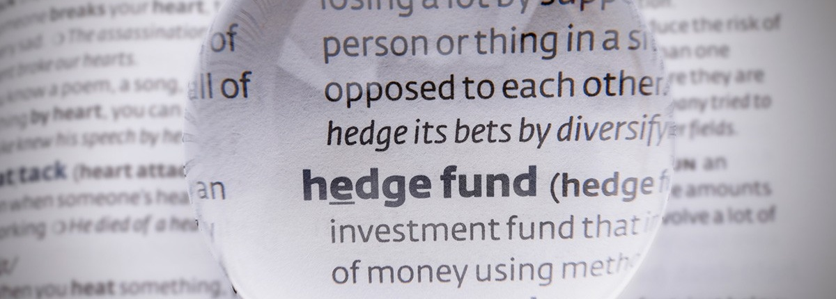 Hedge fund definition in a dictionary under a magnifying glass.