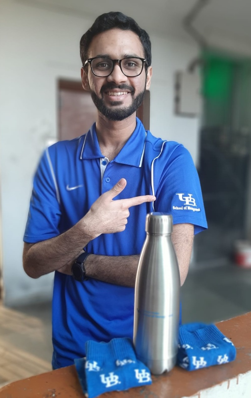 Siddharth Khandelwal shows off the new UB School of Management-branded polo, socks and water bottle he won.