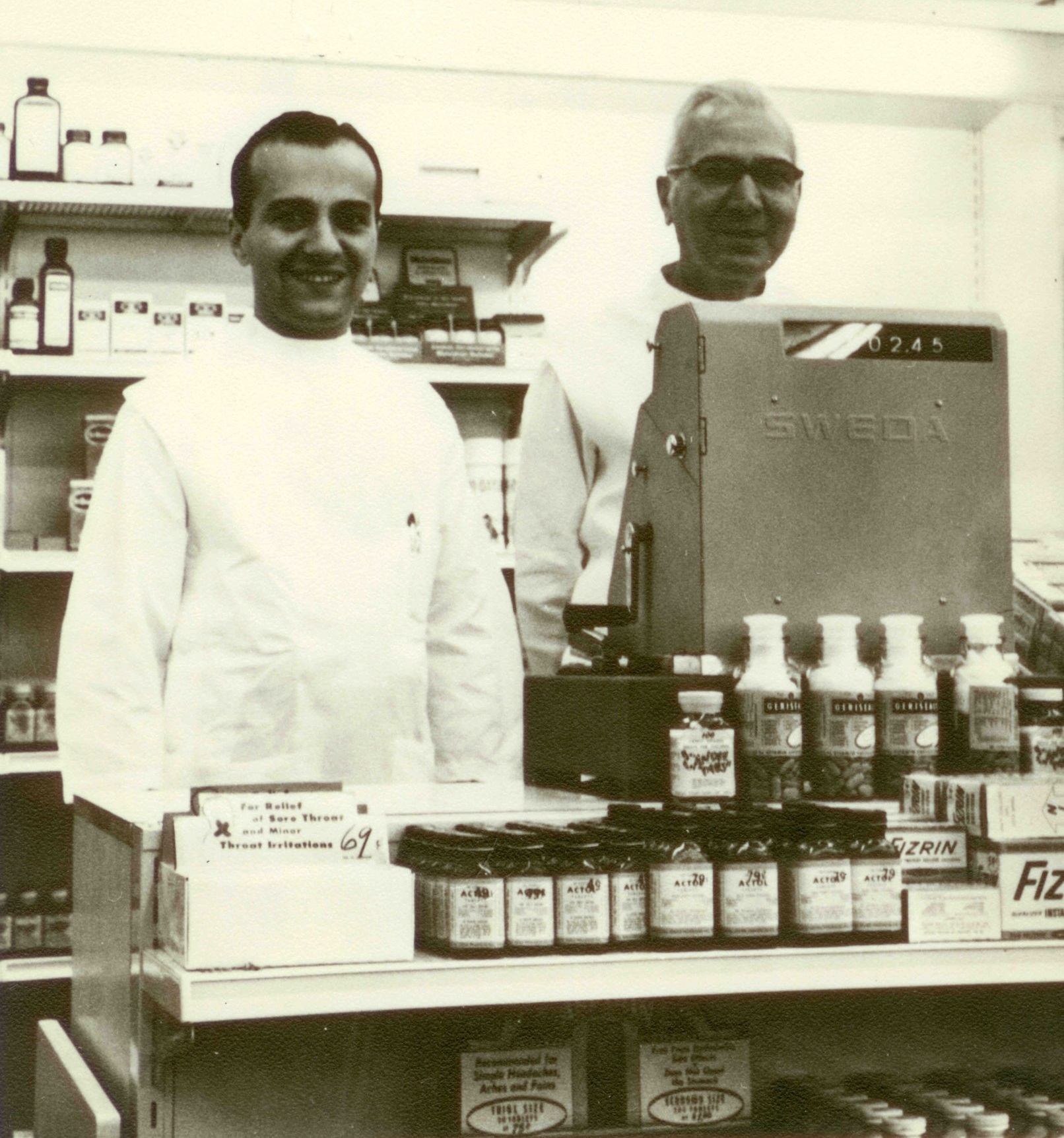 Henry Panasci Jr., and his father, Henry Panasci Sr., behind the counter at the first Fay's Drug Store in Syracuse, New York, in 1958.