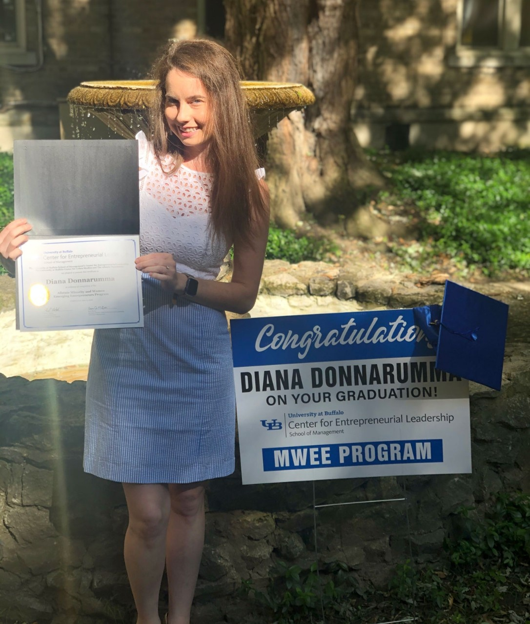 Donnarumma poses with her certificate of completion, graduation cap and a lawn sign congratulating her on graduating from the MWEE program.