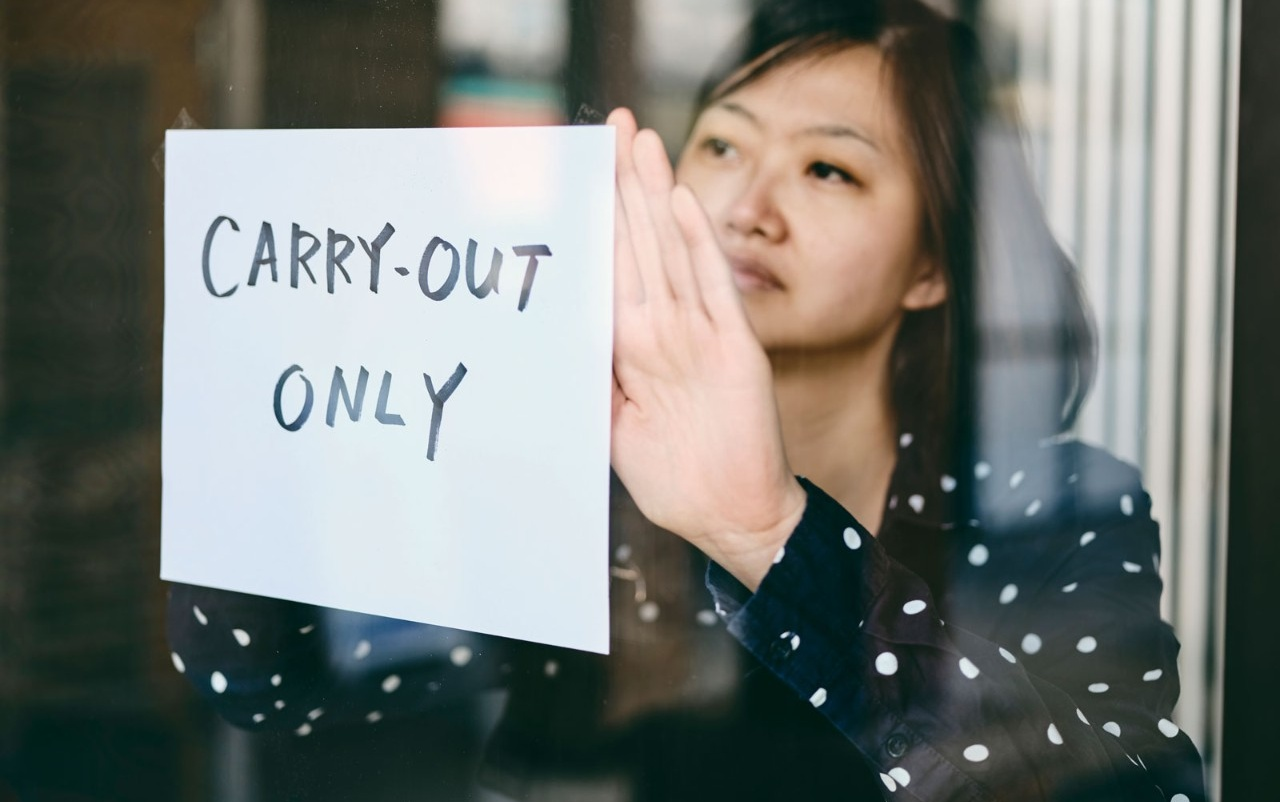 "Business owner hanging a sign that says ""carry-out only.""."