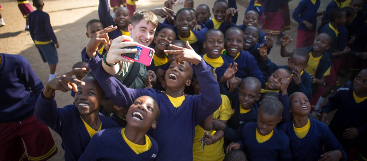 Dylan McCaffrey, business administration student, with schoolchildren in Tanzania during a social innovation-focused experiential learning trip.