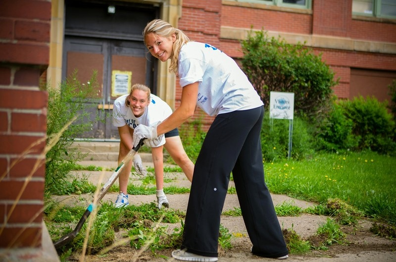First-year MBA students Kristen Sharkey and Dana Musil pull up weeds at the old Campus North PS 63.