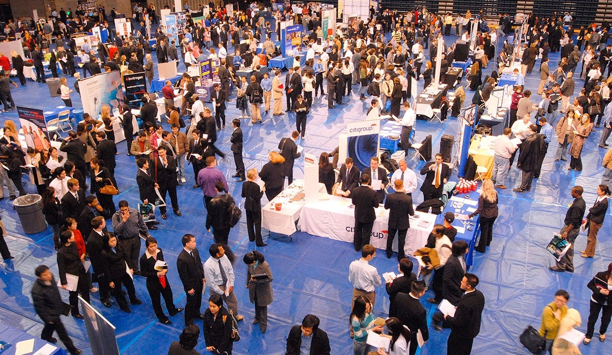 Image of a career fair event with crowds of students visiting company tables.