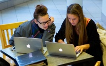 Photo of two students sitting at a desk looking at laptop computers.