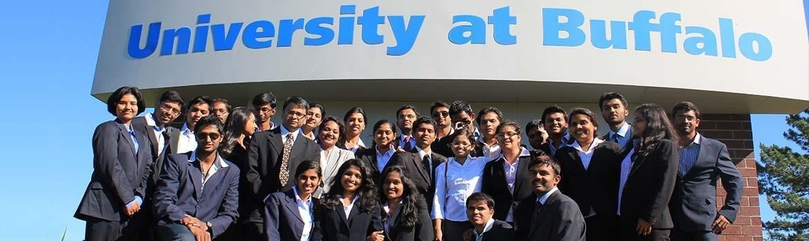 Group photo of students from India in front on a UB sign on their visit here.