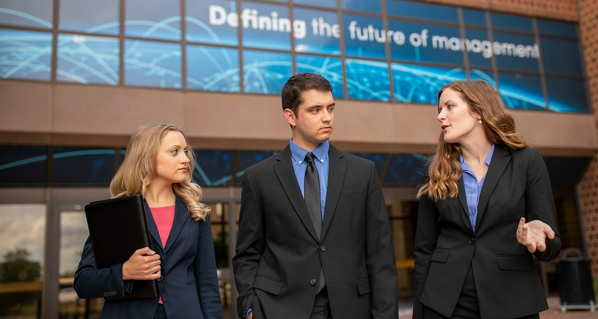 Three MBA students walking outside the Jacobs Management Center.
