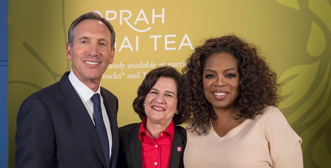 Alum in center of photo with former Starbucks CEO and media mogul Oprah Winfrey.