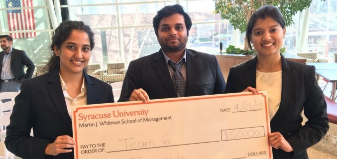Two female students and one male student who won the 2018 Whitman Case Competition holding a large fake check for $5,000.
