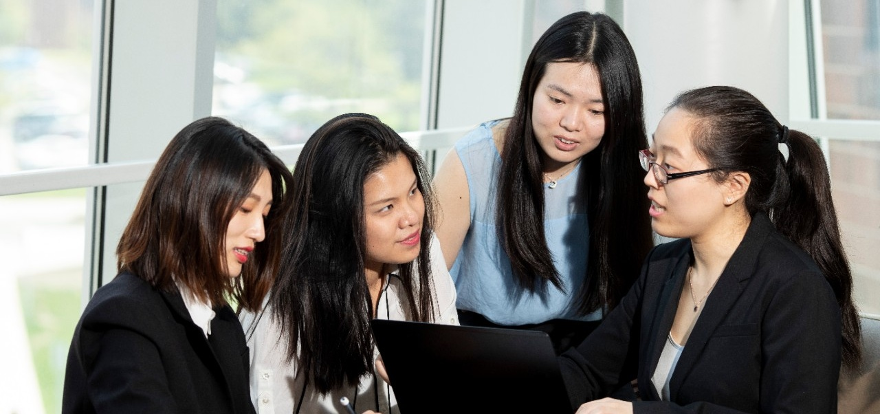 Four Asian School of Management students talking with each other behind a laptop computer.