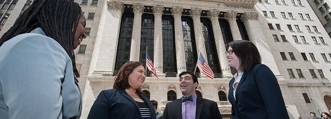 Four students dressed in professional business attire standing outside of a Wall Street building in New York City.