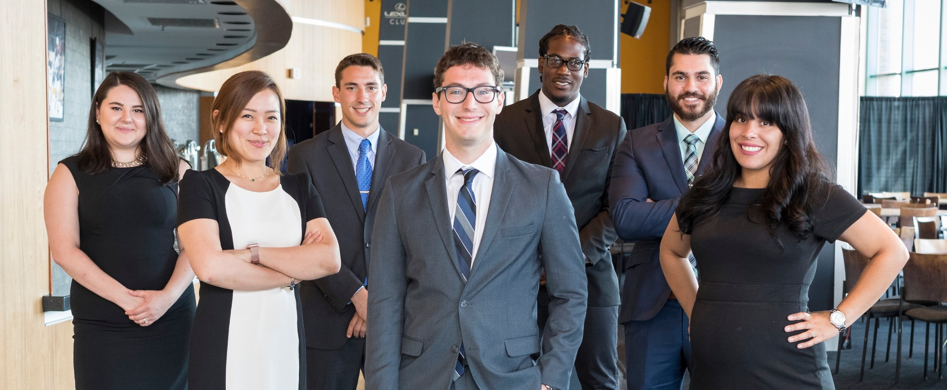 Seven MBA students dressed in professional business attire standing and looking at the camera.