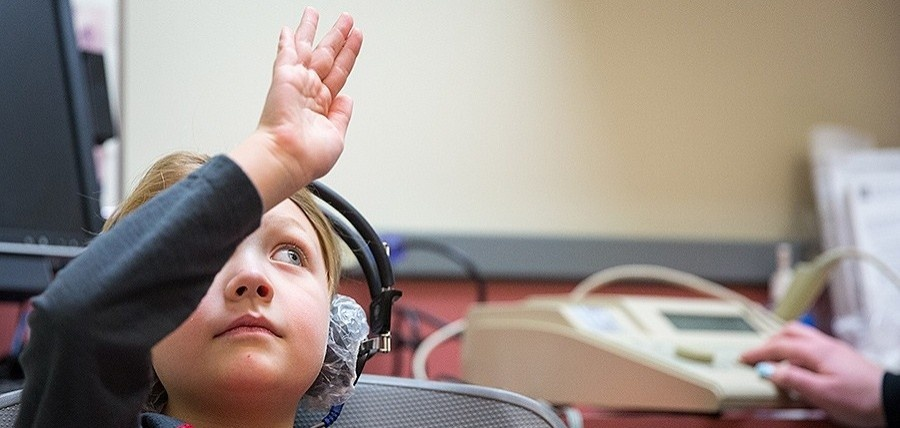 Young student in an audiology clinic raising their right hand.