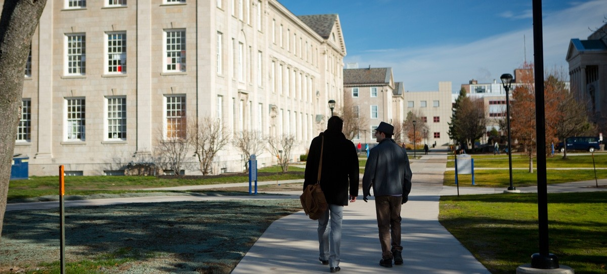 Two students with backs to camera walking in front of Hayes Hall on the South Campus.