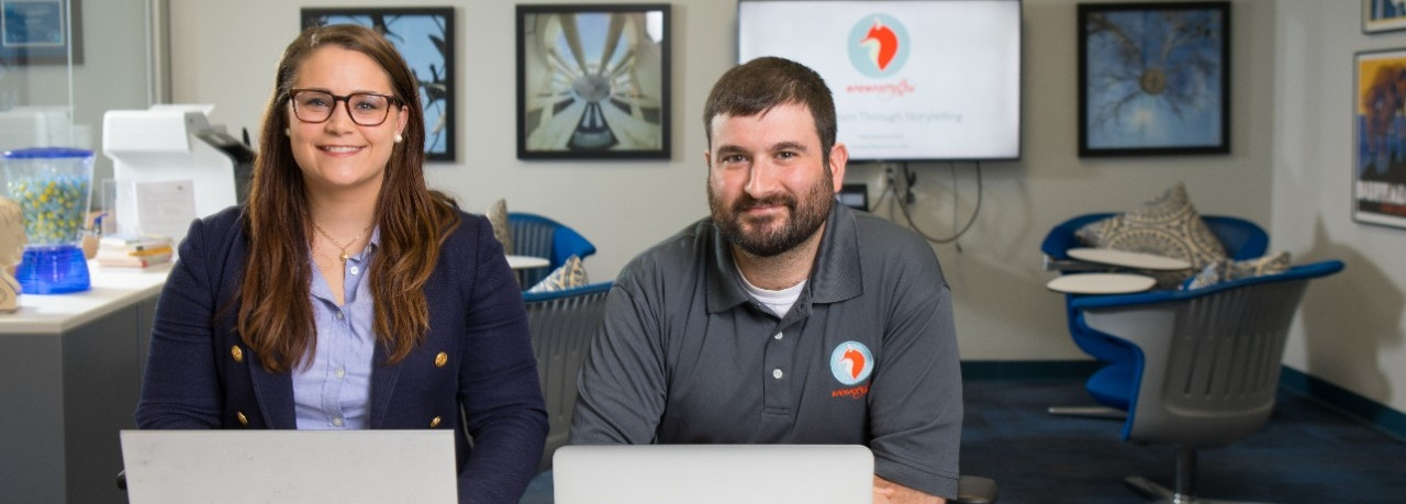 Female student on left of photo and male student on the right of the photo. Both are sitting behind laptops in an office and are looking at the camera.