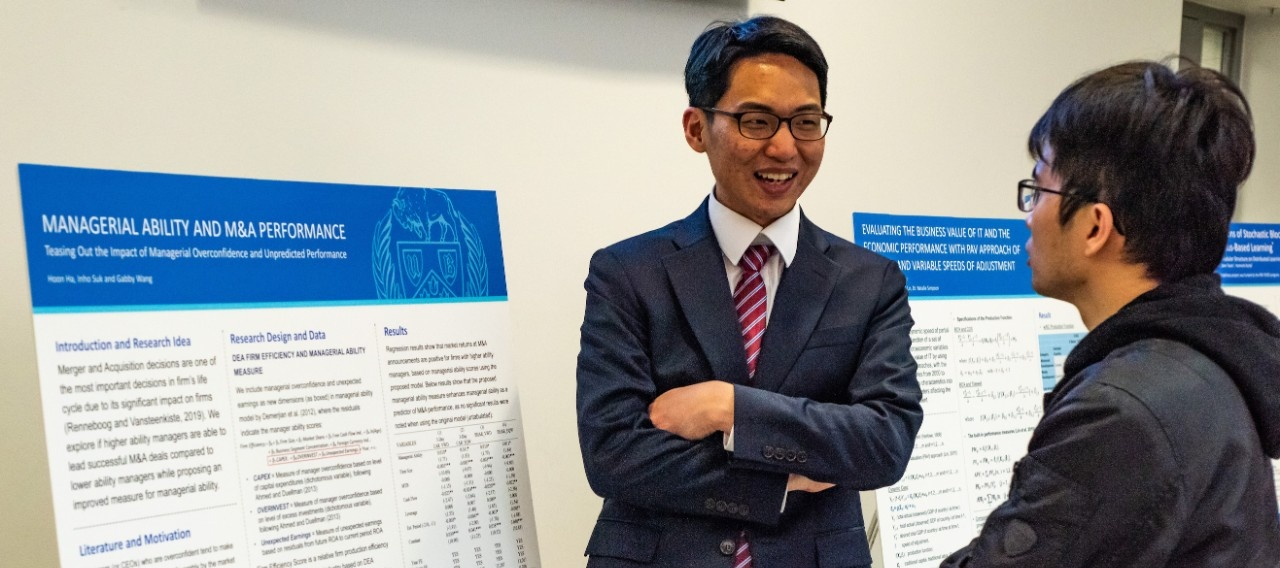 Finance PhD student discussing his work at the PhD Showcase poster presentation.