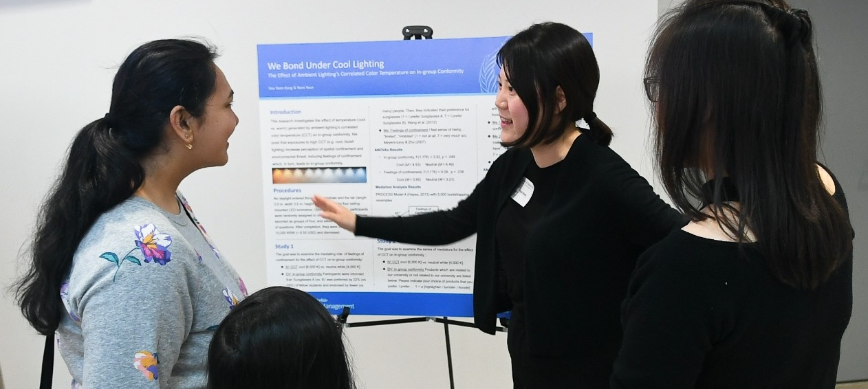 PhD in Management student discussing her research at the PhD Showcase poster presentation.