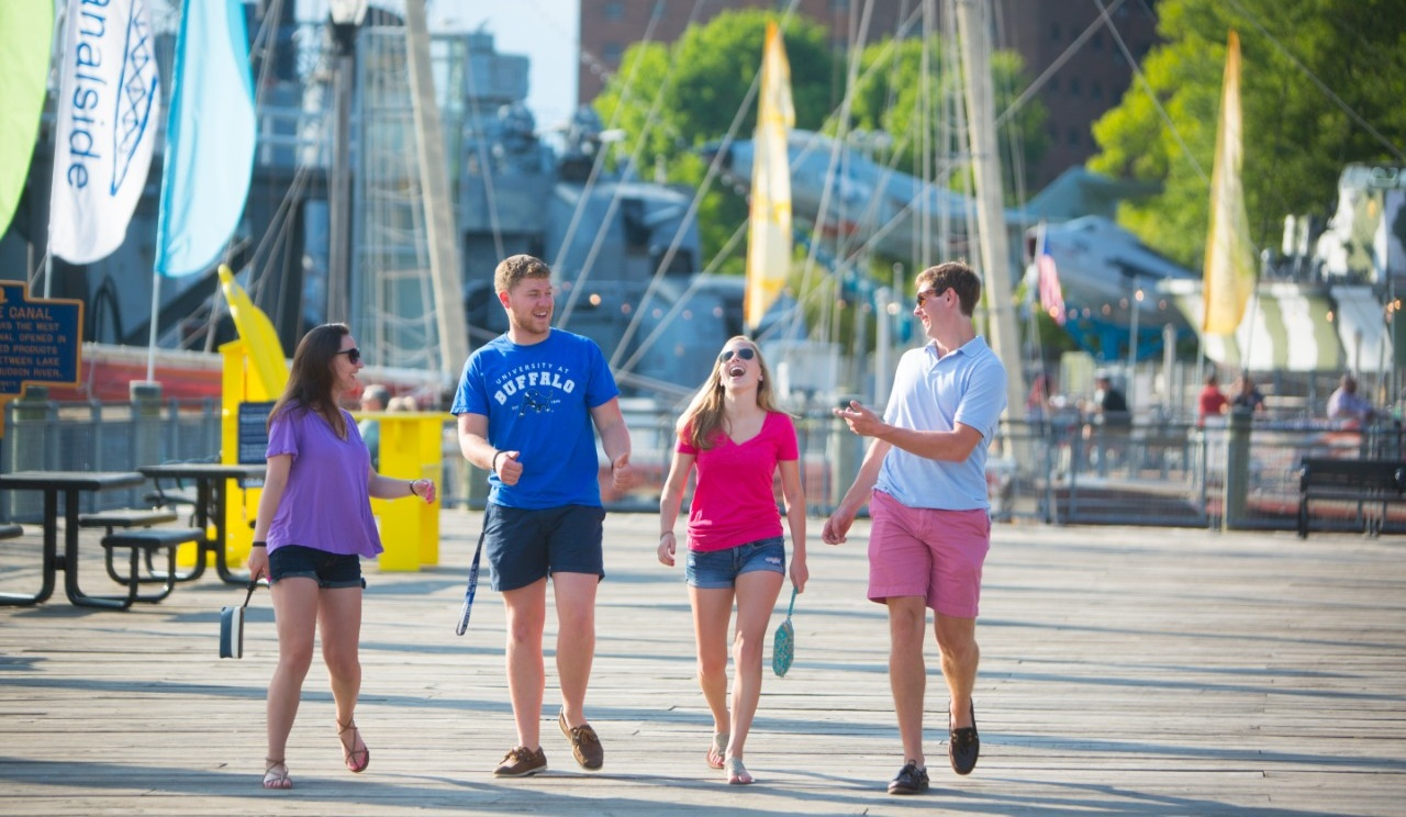 Four individuals walking along the boardwalk at Canalside.