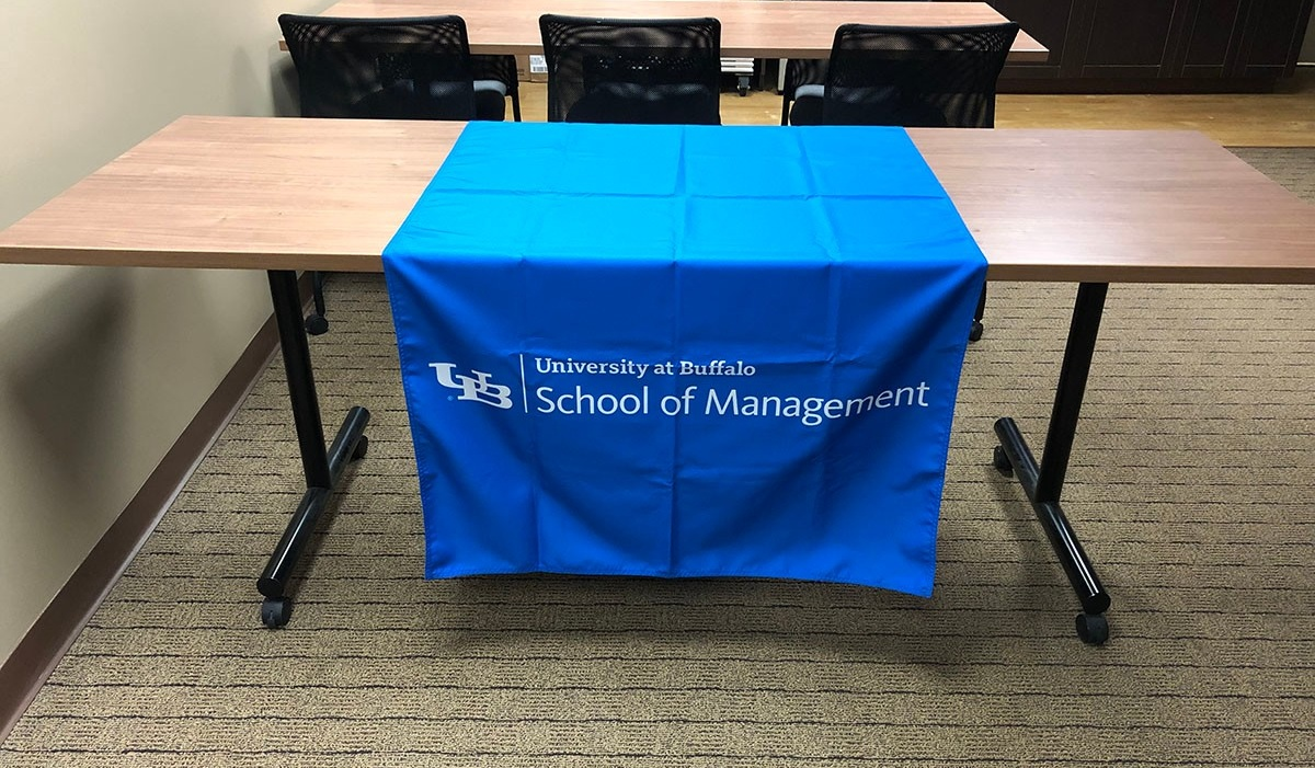 School of Management logo in white on a blue table runner.