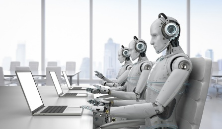 Robots sitting at computers in a call center.