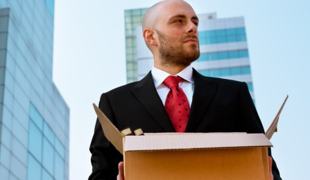 Businessman standing outside in a city holding a box.