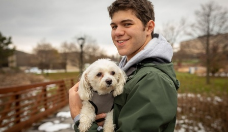 UB School of Management student Michael Nejame holds Millie the dog.