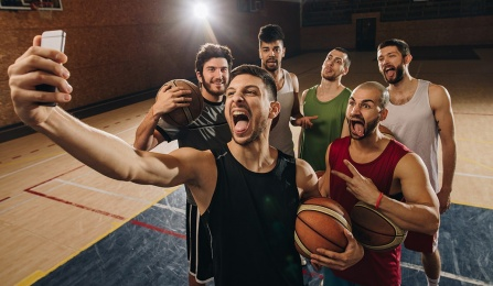 Basketball team on the court taking a selfie.