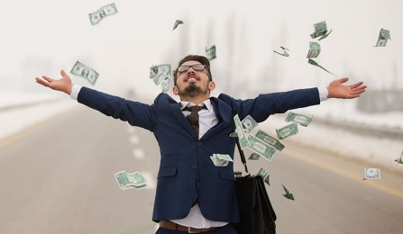 Picture of a dreamer student with arms outstretched and money falling from the sky