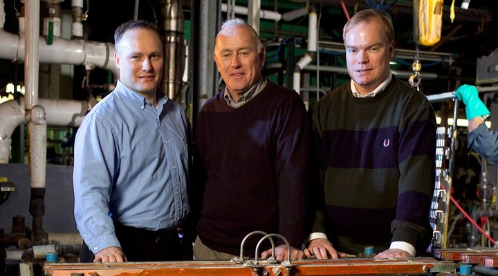 Three older men standing in a factory.