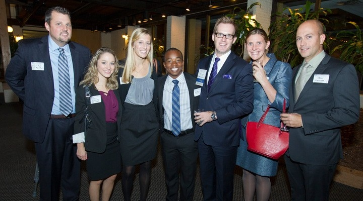 Seven young Alumni dressed in professional attire at an event.