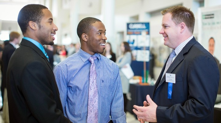 Two African American students on left talking with a prospective employer on right.