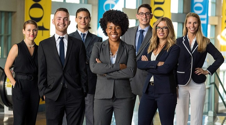 Seven MBA students dressed in professional attire.