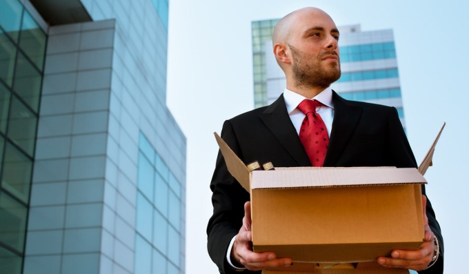 Man in business suit holding a box with skyscrapers in the background.