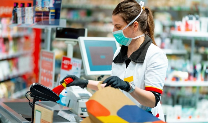 Woman cashier in mask and gloves working at the register.