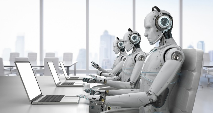 Robots in a call center sitting at a table in front of laptops.
