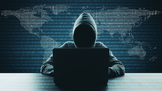 Hacker using laptop on abstract binary code map background.