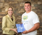 Cynthia Shore, senior assistant dean for alumni and external relations, presents Christopher Sanfilippo from Orchard Park High School with an iPad for achieving the highest individual score in the 2013 MoneySKILL @ School personal finance competition.