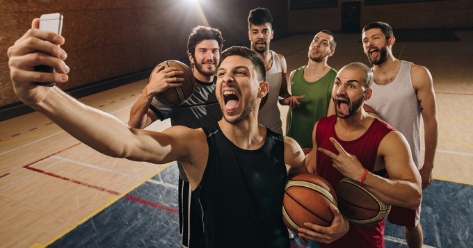 Group of basketball players making faces while taking a selfie on the court.