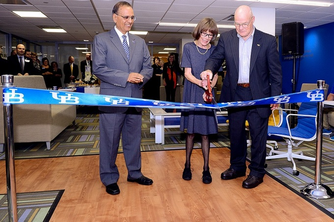 President Satish Tripathi looks on as Frank and Marilyn Clement cut the ribbon officially opening the Undergraduate Learning and Community Center.